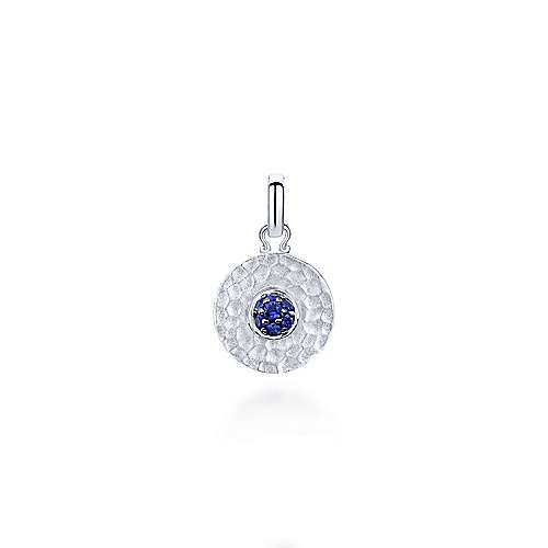 This charming pendant by Gabriel & Co., New York, features a vibrant cluster of sapphires at the center of a chic hammered silver disc.