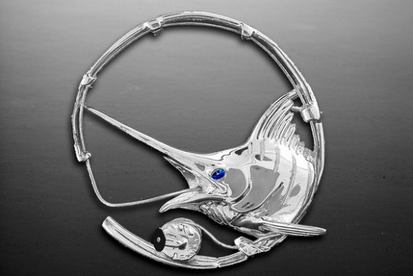 Sterling Silver Marlin Rod and Reel Pendant or Broach/Pin. Has a .05ct. blue sapphire eye and black coral handle on reel.