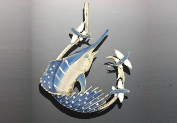 14K yellow gold Sailfish within a circle hook busting flying fish. Sailfish has a .02ct. sapphire eye. Ceramic color. Measures 1.5 inch tall.