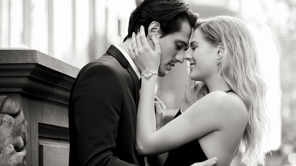 a couple getting engagement, the man is in a black suit, she is in a black evening dress, Gabriel & Co. engagement rings