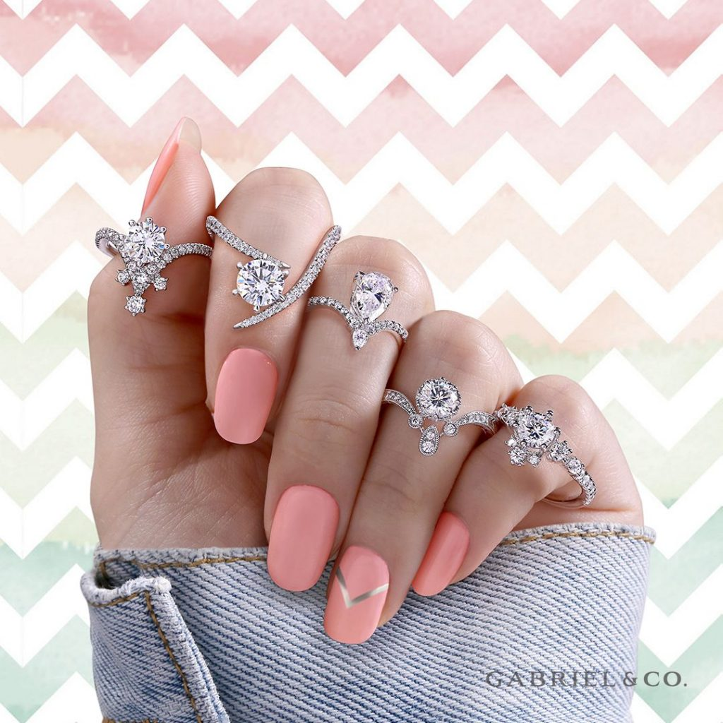 woman's hand with pink nail polish and jeans jacket, wearing a variety of engagement rings, Gabriel & Co. bridal jewelry, engagement rings near me